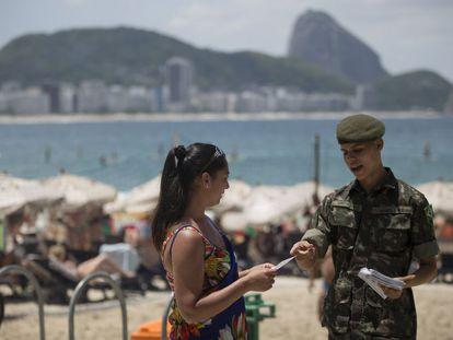 Soldado reparte panfletos informativos sobre o Zika em Copacabana.
