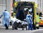 Health workers wear PPE as they transfer a patient into from an ambulance into The Royal London Hospital in east London on April 18, 2020, during the novel coronavirus COVID-19 pandemic. - Britain's death toll from the coronavirus rose by 847 on Friday, health ministry figures showed, a slightly slower increase than the previous day but still among the worst rates globally. (Photo by DANIEL LEAL-OLIVAS / AFP)