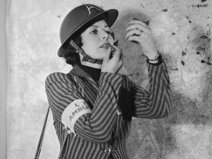 Membro de grupo de prevenção contra ataques aéreos do Reino Unido se maquia, por volta de 1940.