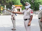 Punjab Police personnel stand guard after strict lockdown norms for weekends and public holidays were imposed as a preventive measure against the COVID-19 coronavirus, in Amritsar on June 13, 2020. (Photo by NARINDER NANU / AFP)