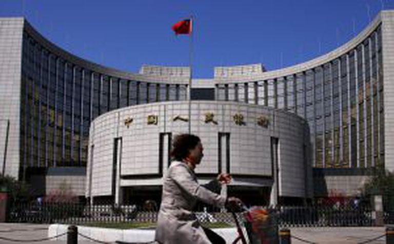 Mulher passa em frente à sede do Banco Popular da China, em Pequim.