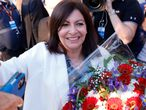 Paris mayor Anne Hidalgo gets a bouquet of flowers after her victorious second round of the municipal election, Sunday, June 28, 2020 in Paris. France on Sunday held the second round of municipal elections that has seen a record low turnout amid concerns over the coronavirus outbreak and anger at how President Emmanuel Macron's government handled it. (AP Photo/Christophe Ena)