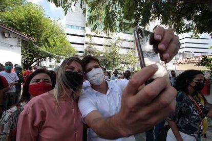 O candidato à prefeitura do Recife João Campos (PSB) tira foto com apoiadoras.