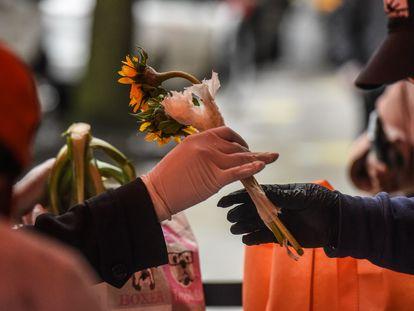 Mulher recebe flores e mantimentos durante ação social no Harlem, em Nova York, para o Dia das Mães.