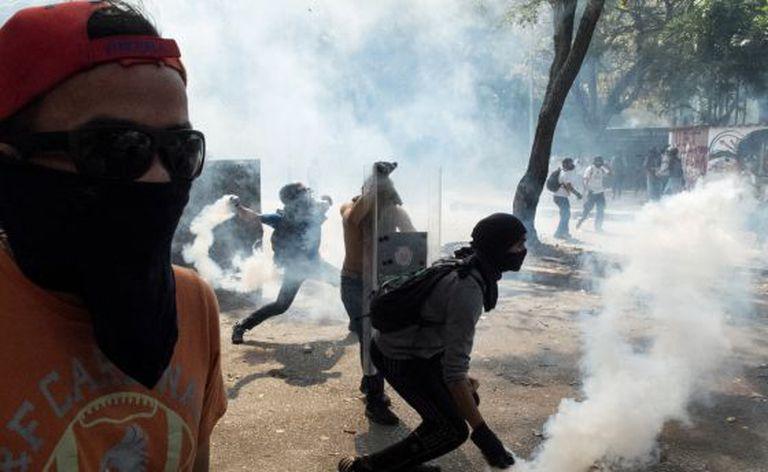 Manifestantes jogam de volta bombas de gás lacrimogêneo à polícia durante um protesto contra o Governo, na quarta-feira em Caracas.
