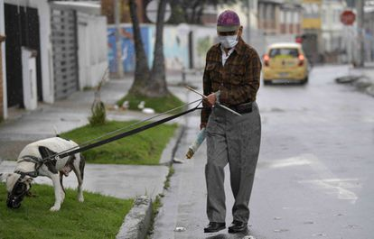 Um homem usa uma máscara facial como medida preventiva contra a propagação do novo coronavírus, enquanto passeava com seu cachorro em Bogotá, em 16 de março de 2020.