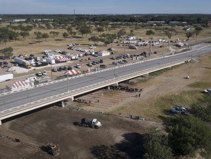 Vários caminhões limpam o terreno onde ficava o acampamento de imigrantes haitianos sob a Ponte Internacional Del Río (Texas), nesta sexta-feira. No vídeo, Biden admite responsabilidade PELA crise da fronteira.