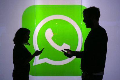 Duas pessoas usam seus celulares em frente ao logo do WhatsApp em Londres.