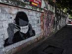 """AME8258. RÍO DE JANEIRO (BRASIL), 22/06/2020.- Vista este lunes de un grafiti que muestra al presidente de Brasil, Jair Bolsonaro, mientras se coloca un tapabocas con la inscripción """"Covard-17"""", en crítica a su manejo de la pandemia COVID-19 y en referencia al número que utilizó durante la campaña presidencial, en Río de Janeiro (Brasil). Brasil llegó este lunes a casi 51.000 muertos por coronavirus y 1,1 millones de enfermos, en medio de una crisis sanitaria que convive con las serias turbulencias políticas desatadas en torno al Gobierno del ultraderechista Jair Bolsonaro. EFE/Antonio Lacerda"""