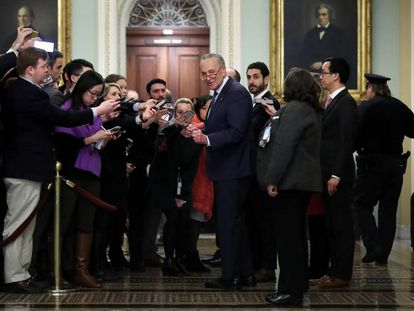 Chuck Schumer, líder da minoria democrata do Senado, cercado por jornalistas.