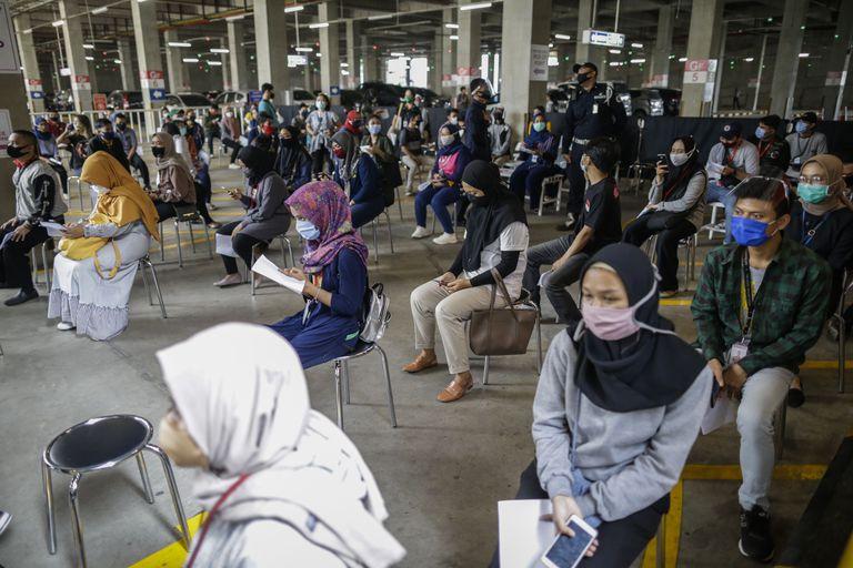 Funcionários de um shopping de Tangerang, na Indonésia, aguardam para serem testados para o coronavírus.