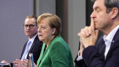 Merkel fala à imprensa na manhã desta terça-feira, com o prefeito de Berlim, Michael Müller, à direita, e o governador da Baviera, Markus Söder, à esquerda.