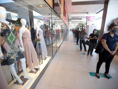 Dezenas de pessoas com máscaras fizeram fila, nesta quarta-feira, em um centro comercial de Brasília, que abriu seguindo uma série de requisitos de saúde para prevenir a disseminação do coronavírus.