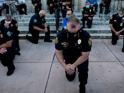 Policiais se ajoelham durante manifestação em Coral Gables, (Flórida), no domingo.