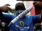 A man holds a mock syringe as demonstrators protest against Sao Paulo state governor Joao Doria and China's Sinovac potential coronavirus disease (COVID-19) vaccine in Sao Paulo, Brazil, November 1, 2020. REUTERS/Amanda Perobelli