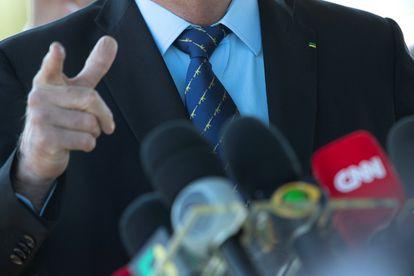 Detalhe da gravata do presidente Jair Bolsonaro estampada com desenhos de rifles.