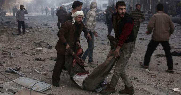 Sírios carregam vítima de bombardeio em Damasco.