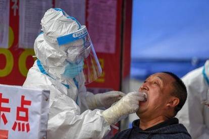 Um profissional sanitário faz exame de coronavírus em um morador da cidade de Shulan, no nordeste da China.