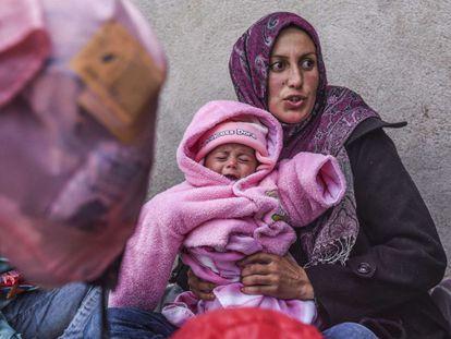 """A Europa está sofrendo a maior onda de imigrantes desde a Segunda Guerra Mundial, e estima-se que mais da metade dos deslocados vêm da Síria. Milhares de refugiados e migrantes provenientes deste e de outros países em guerra estão sofrendo bloqueios perto dos postos fronteiriços na Hungria, Croácia, Sérvia e Eslovênia, devido aos contínuos fechamentos de fronteiras e também às limitações impostas por alguns desses países, segundo denúncia da organização Médicos Sem Fronteiras. Na foto, um bebê com um gorrinho que diz """"Princesa Dora"""" chora nos braços de sua mãe. Ambas esperam um ônibus para ajudá-las a continuar sua jornada na cidade de Miratovac entre a fronteira sérvia-macedônia, em 22 de outubro."""