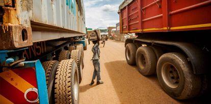 Menino ganha a vida vendendo água mineral aos caminhoneiros que esperam na fila. Martin Kharumwa.