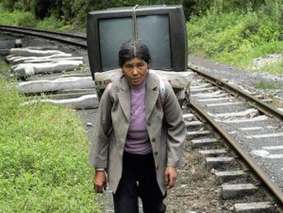 Uma mulher carrega uma televisão em Sichuan.