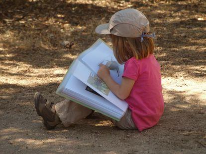 A natureza te permite conectar, mas também investigar e manter ativos os processos de curiosidade. Na imagem, uma menina observa atentamente um bicho que encontrou em um dia de escola no grupo de jogos do Naturaleza Saltamontes, em Madri.