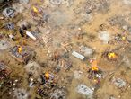 In this aerial picture taken on April 26, 2021, relatives and friends of a victim who died of the Covid-19 coronavirus gather to cremate the body at a cremation ground in New Delhi. (Photo by Jewel SAMAD / AFP)