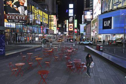 Mulher trafega em uma Times Square quase vazia, em Nova York, na noite de segunda.
