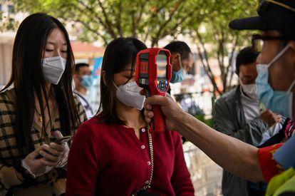 Controle de temperatura em passageiros recém-chegados na estação de trem de Hankou, em Wuhan.