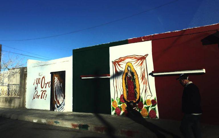 Um mural com imagem da virgem de Guadalupe sobre a bandeira mexicana em Ciudad Juárez.