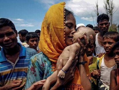 Uma mulher chora enquanto segura seu filho que morreu afogado quando um bote em que estavam virou antes de chegar a Bangladesh.