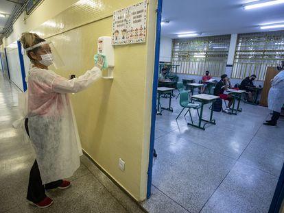 Mãe de aluno, contratada em um programa de temporários da Prefeitura, desinfeta um recipiente de álcool gel na escola de ensino fundamental Sylvia Martin Pires em São Paulo, em 8 de março de 2021.