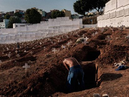 Um coveiro exausto cava uma cova no cemitério do Pechincha na zona Oeste do Rio de Janeiro.