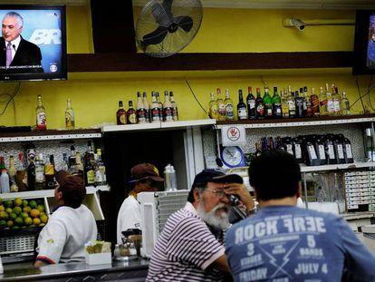 Trabalhadores assistem em um bar a um pronunciamento de Michel Temer da TV.