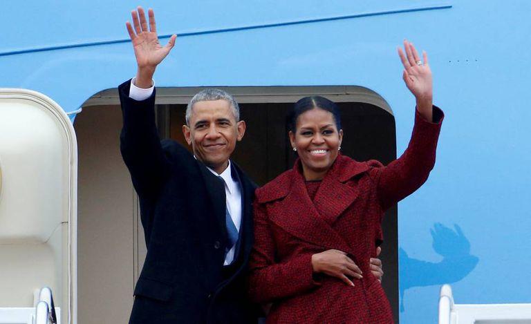 Barack e Michelle Obama acenam ao descer de um avião em janeiro de 2017.