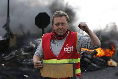 Um sindicalista olha para a câmera após criar uma barricada para impedir o acesso a uma refinaria durante a greve em Douchy les Mines, norte da França.