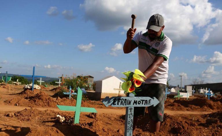 Familiar coloca cruz para identificar o túmulo de uma das vítimas da chacina em Altamira.