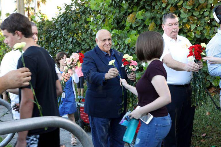 Policiais entregam flores a alunos que regressam ao colégio que foi palco da matança em Parkland.