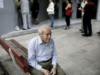Um pensionista, sentado na fila de um caixa na Grécia.