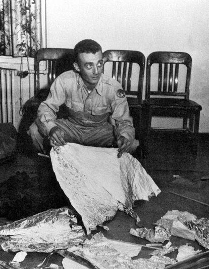 """O comandante Jesse Marcel, oficial de inteligência na base aérea do Exército em Roswell, segura os restos de um """"disco voador"""" encontrado em uma fazenda de criação de ovelhas a 120 quilômetros de Roswell, Novo México. Marcel afirmava que o material parecia """"não ser desta Terra"""". Foi em julho de 1947."""