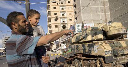 Khalid Shabha e seu filho observam os tanques da avenida Trípoli, em Misrata.