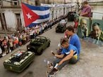 SANTA CLARA, CUBA - DECEMBER 01:  People sit on their rooftop to get a better view as the remains of former Cuban President Fidel Castro pass by on their cross-country journey from Havana to Santiago de Cuba on December 1, 2016 in Santa Clara, Cuba. Castro, the revolutionary leader who brought communism to his island nation in 1959, died November 25 at the age 90 years old.  (Photo by Chip Somodevilla/Getty Images)