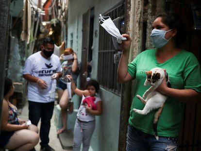 Mulkher acena com máscara cedida pela Central Única das Favelas (CUFA)em Heliópolis, São Paulo, Brazil, em 18 de junho.