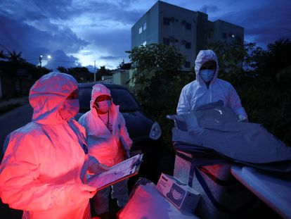 Agentes de saúde municipais se preparam para examinar o corpo de uma pessoa em meio ao surto de coronavírus em Manaus.