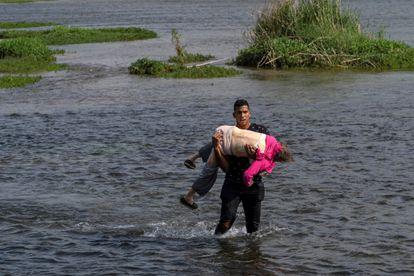 Um migrante venezuelano cruza o rio Grande, na fronteira entre os EUA e o México, carregando uma idosa, na quarta-feira.