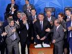 O presidente da República, Jair Bolsonaro, assina o decreto que afrouxa controle de armas, em 2019.