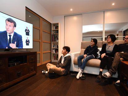 Uma família assiste na televisão o pronunciamento de Emmanuel Macron sobre as novas medidas de restrição para conter a covid-19 na França.