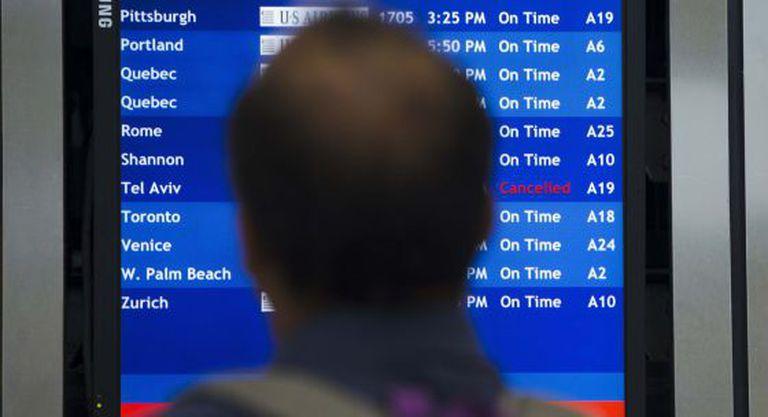 Um homem consulta a lista de voos no aeroporto da Filadélfia.