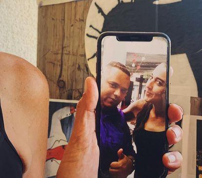 Karina Spinoza mostra, no celular, uma foto sua com o amigo Diego Pereira, uma das 100.000 vítimas da covid-19 no Brasil.