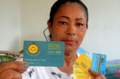 Ermanda Maria de Sena, a primeira usuária cadastrada do Bolsa Família, mostra o cartão do Bolsa-Alimentação com o número 01